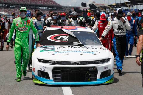 Nascar drivers Kyle Busch, left, and Corey LaJoie, right, join other drivers and crews as they ...
