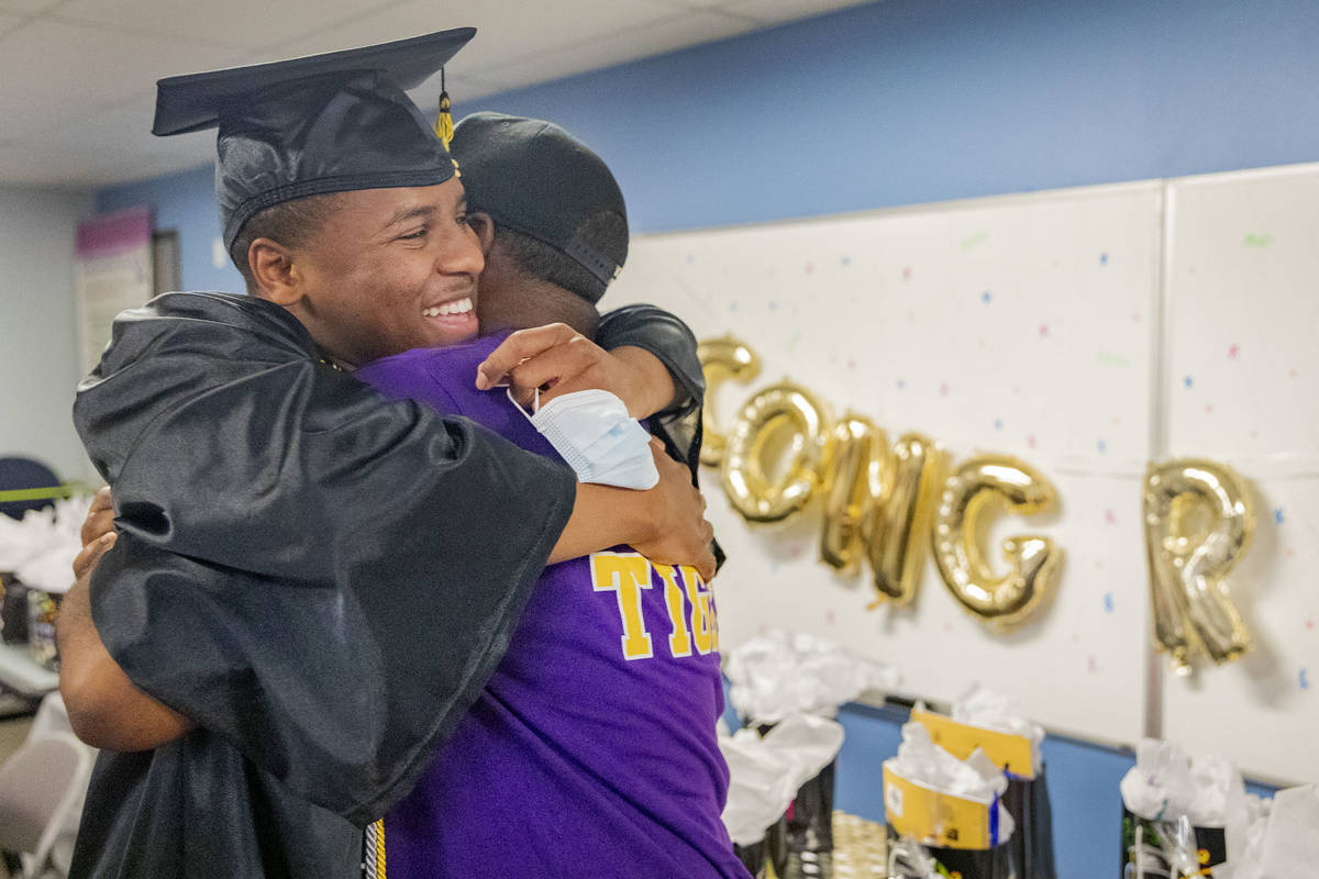 Jaden Hines, 18, a graduate of Nevada State High School, left, hugs his foster parent Joseph Wi ...