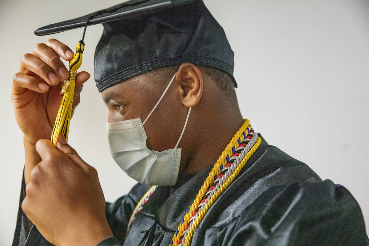 Jaden Hines, 18, a graduate of Nevada State High School, puts on his cap and gown for a graduat ...