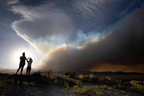 Amy Mojica, left, and her father Mauricio Mojica, take photos as the Mahogany Fire burns behind ...