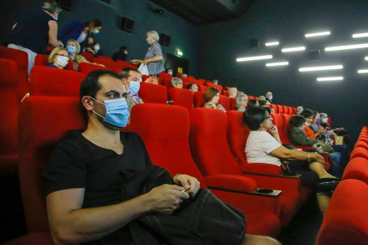 People wear protective masks as they wait for the screening of a movie in Paris, Monday, June 2 ...