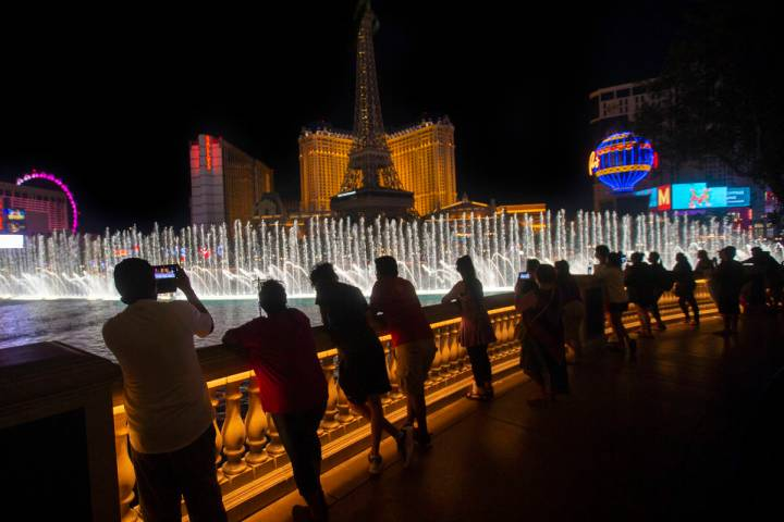 Entertainers from Mystique Showgirls watch the Fountains of Bellagio on the Strip on Wednesday, ...