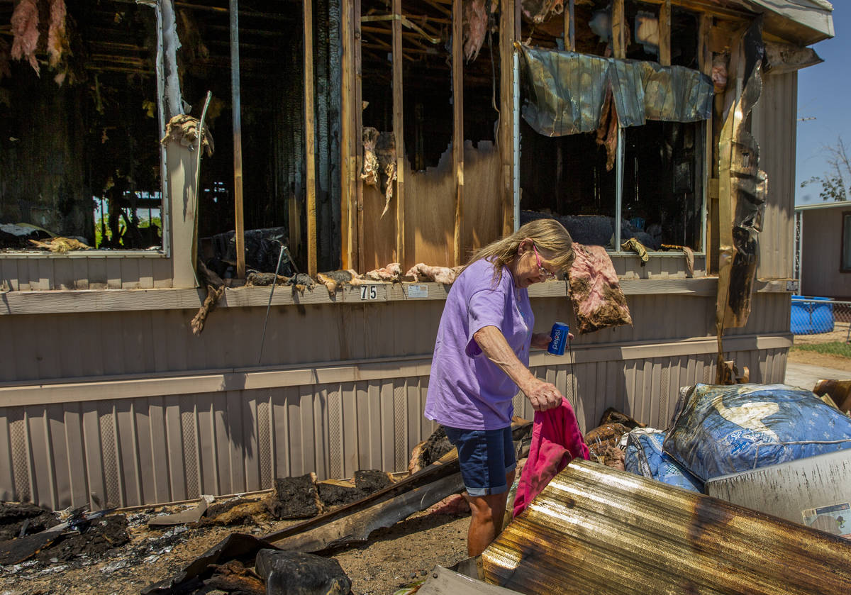 Claudia Arevala sorts through the remains of a fire in her home at the Town and Country Mobile ...