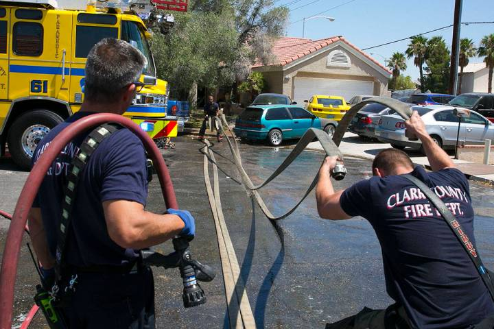 The Clark County firefighters wrap up after battling a shed fire that spread to the home in the ...