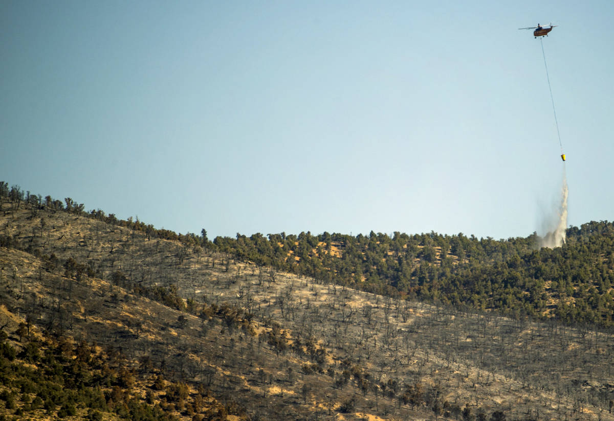 A helicopter with water bucket makes another drop over the Mahogany Fire on Mount Charleston on ...