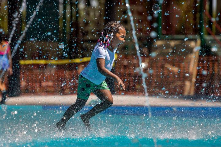 Madison Keyes, 4, runs through the fountains on a waterpad at The Paseos Park on Saturday, July ...