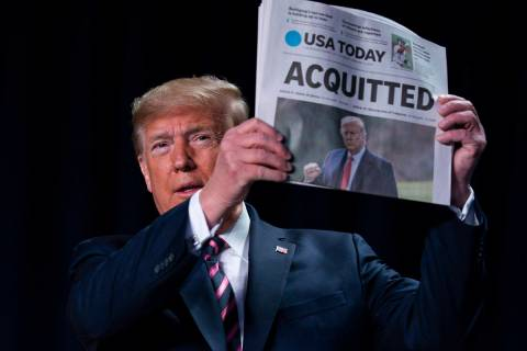 In a Feb. 6, 2020, file photo, President Donald Trump holds up a newspaper with the headline th ...