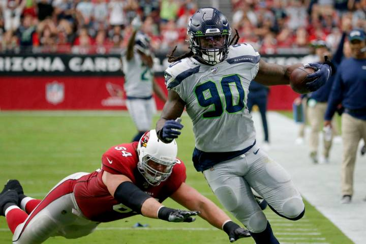 Seattle Seahawks outside linebacker Jadeveon Clowney (90) runs back an interception for a touch ...