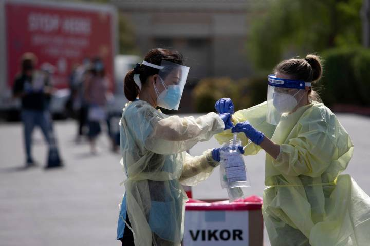 Volunteers place a nasal swab into a container at the COVID-19 drive-through testing site at Ca ...