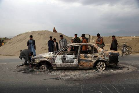 FILE - In this April 9, 2019, file photo, Afghans watch a civilian vehicle burnt after being sh ...
