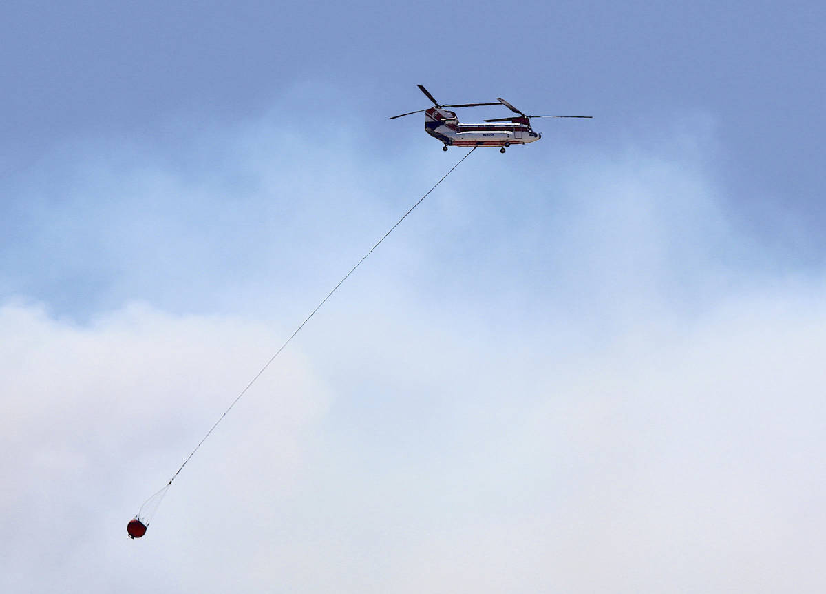 A large firefighting helicopter carries water on on its way to contain the Numbers Fire burning ...