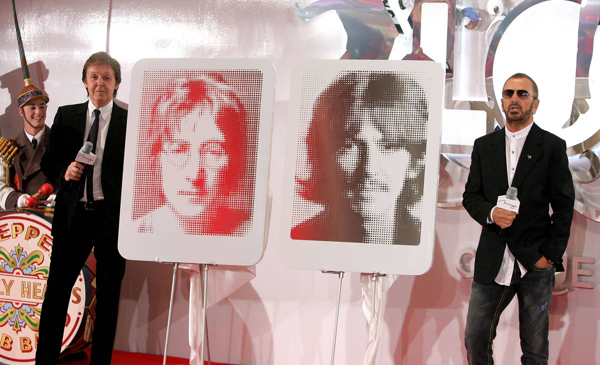 Former members of The Beatles Paul McCartney, left, and Ringo Starr stand next to portraits of ...