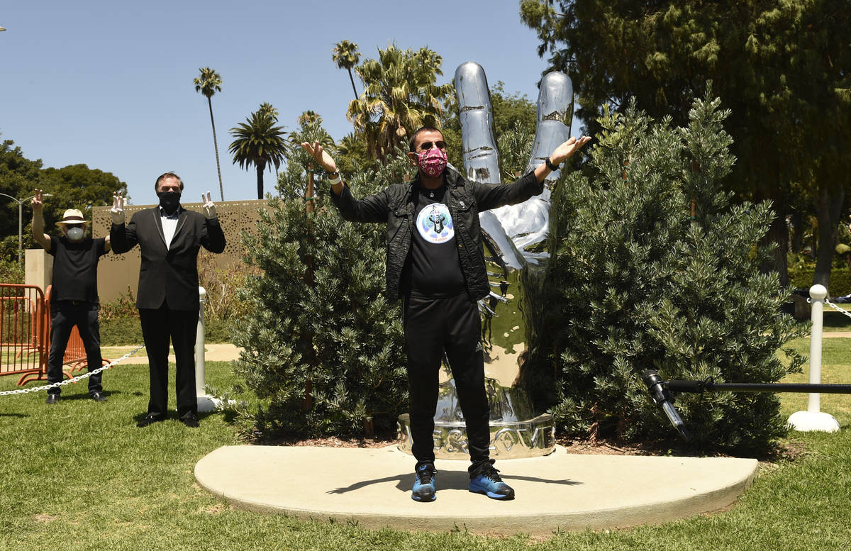 "Musician Ringo Starr poses in front of his ""Peace and Love"" sculpture on his 80th bir ..."