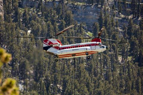 A helicopter with water bucket fills up at the Lee Canyon Ski Resort for another drop over the ...