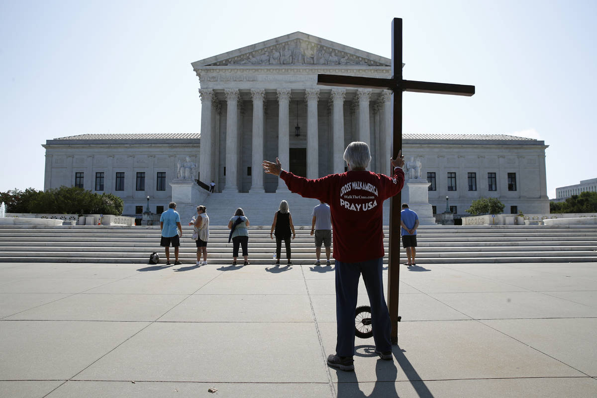 Tom Alexander holds a cross as he prays prior to rulings outside the Supreme Court on Capitol H ...