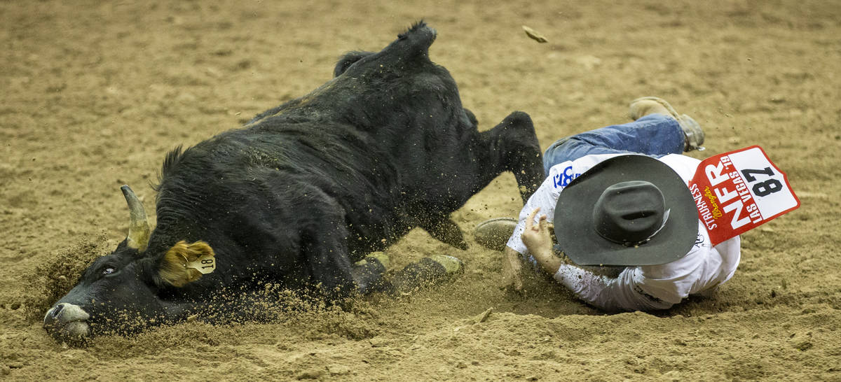 J.D. Struxness of Milan, Minn., mistimes the leap and eats some dirt in Steer Wrestling during ...