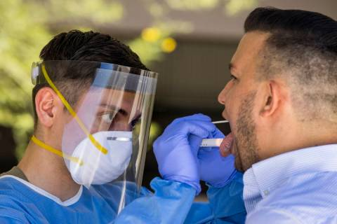 Nevada National Guard soldier PFC Nikolas Herrera, left, inserts a swab into the mouth of Paulo ...
