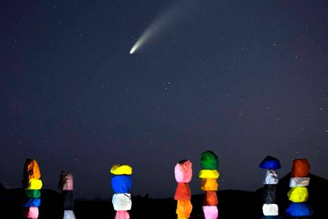 Comet NEOWISE streaks across the sky above the Seven Magic Mountains art installation on Wednes ...