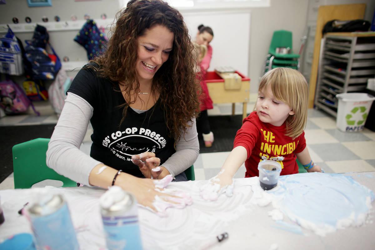 Teacher Bonnie Toth helps Sawyer Karadbil, 3, play with shaving cream in a game designed to dev ...