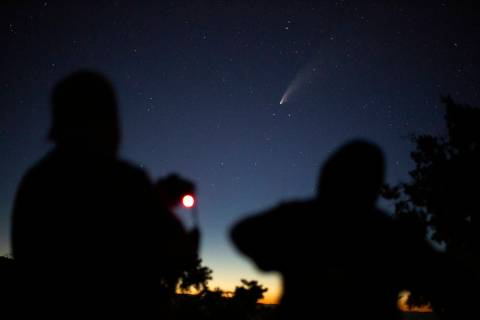 Local photography hobbyist Mike Alder, left, makes a long exposure images of the NEOWISE comet ...