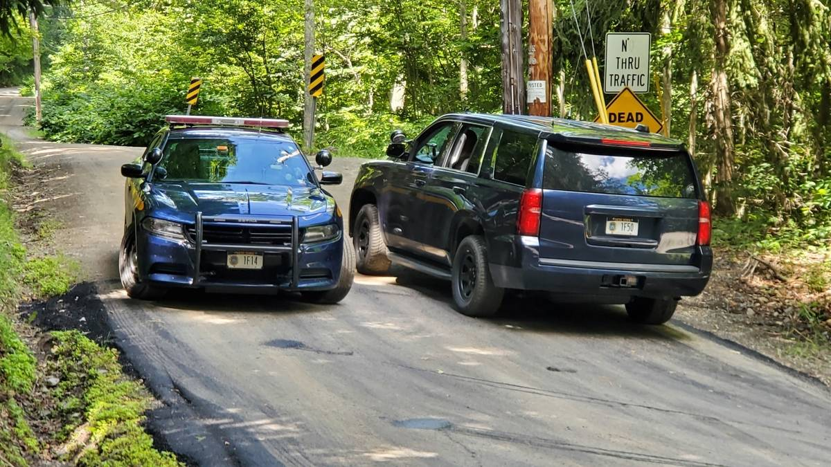 New York State Police block off a road near the scene where the body of Roy Den Hollander was f ...