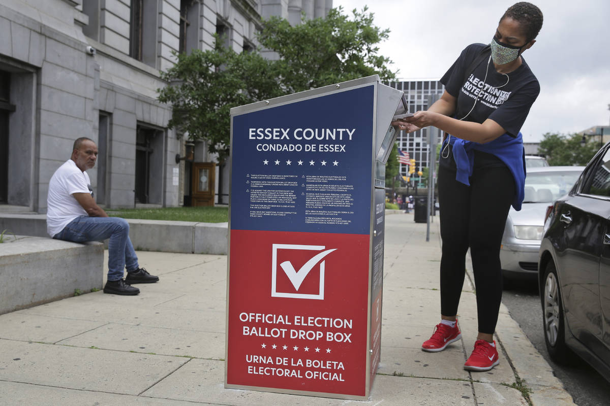 A woman drops her mail-in ballot into a drop box in Newark, N.J., Tuesday, July 7, 2020. New Je ...