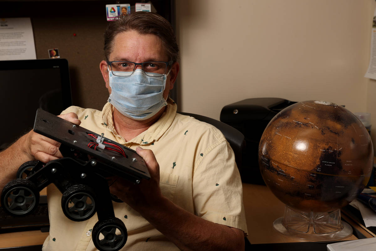 UNLV Professor Christopher Adcock with Mars globe and rover chassis in his office on campus in ...