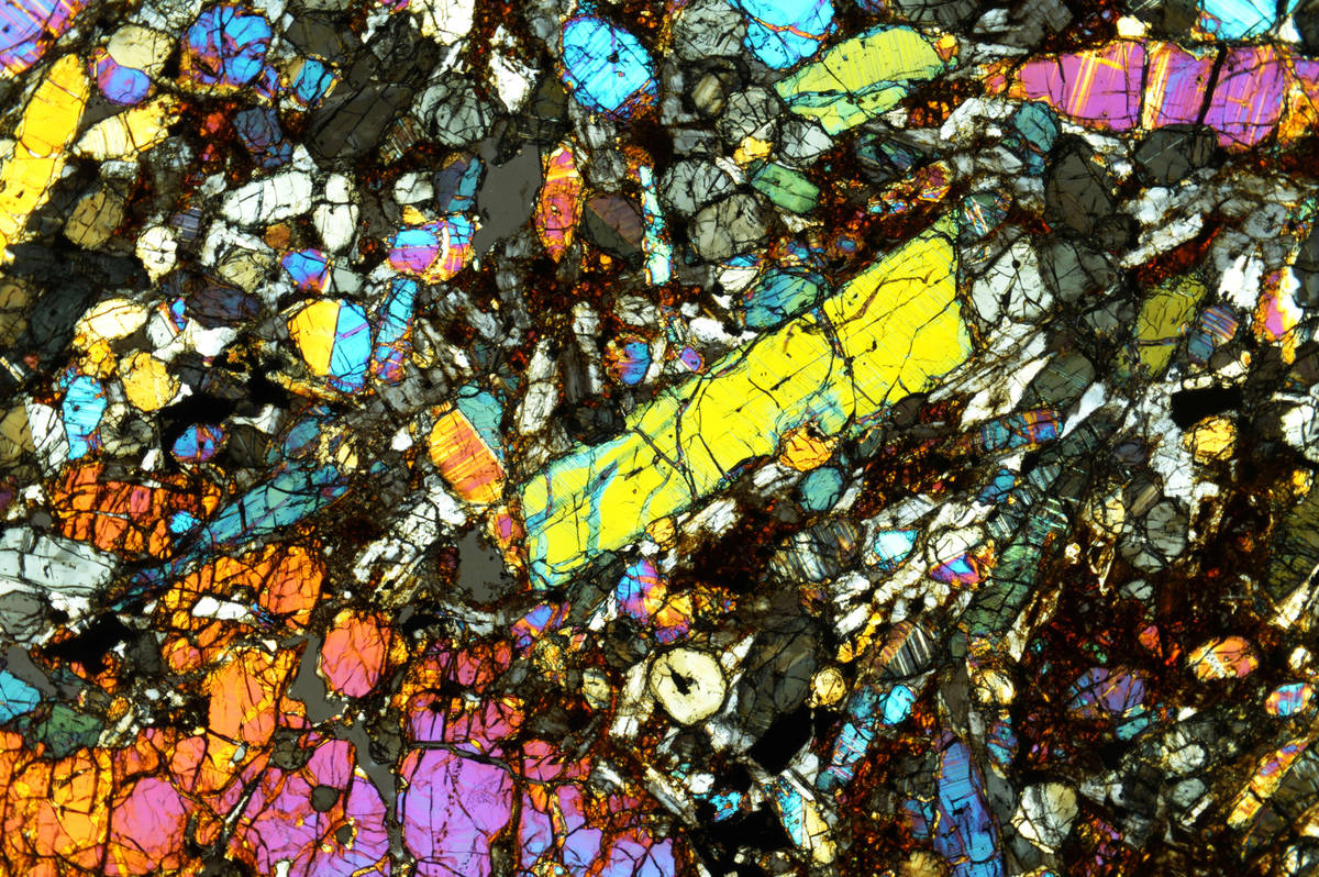 When viewed through polarized light in a microscope, a thin slice of meteorite reveals differen ...