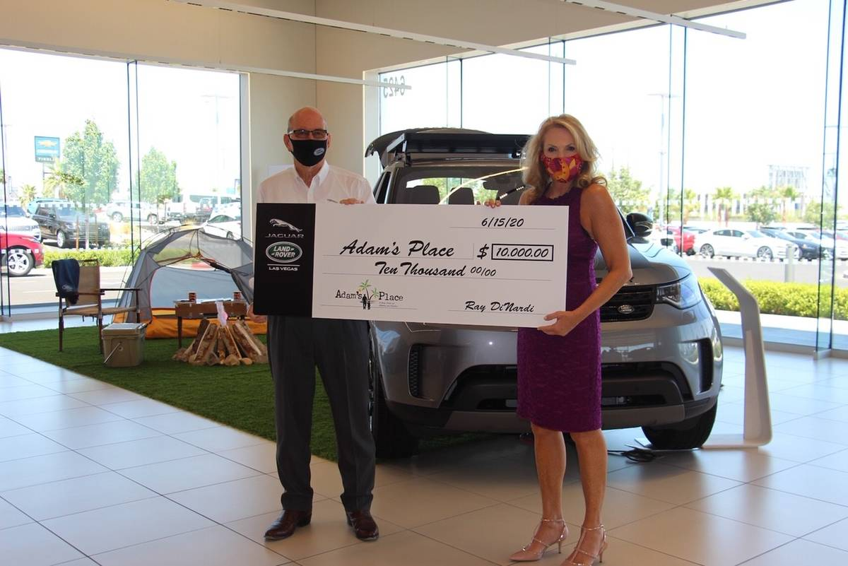 Jaguar Land Rover Las Vegas general manager Ray Dinardi presents check to Adam's Place co-fou ...