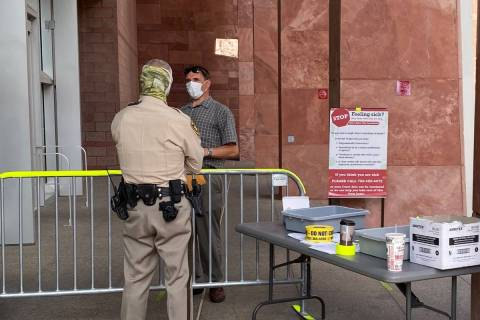 Masked marshals guard the entrance to the Regional Justice Center in Las Vegas, where a mask or ...