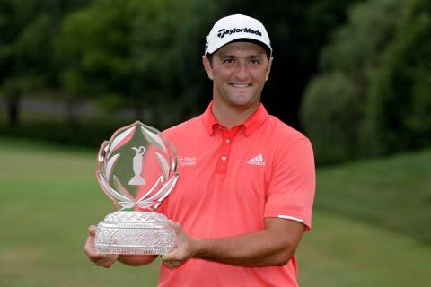 Jon Rahm, of Spain, poses with the trophy after winning the Memorial golf tournament in Dublin, ...
