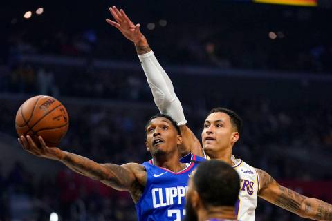Los Angeles Clippers guard Lou Williams, left, shoots as Los Angeles Lakers forward Kyle Kuzma ...