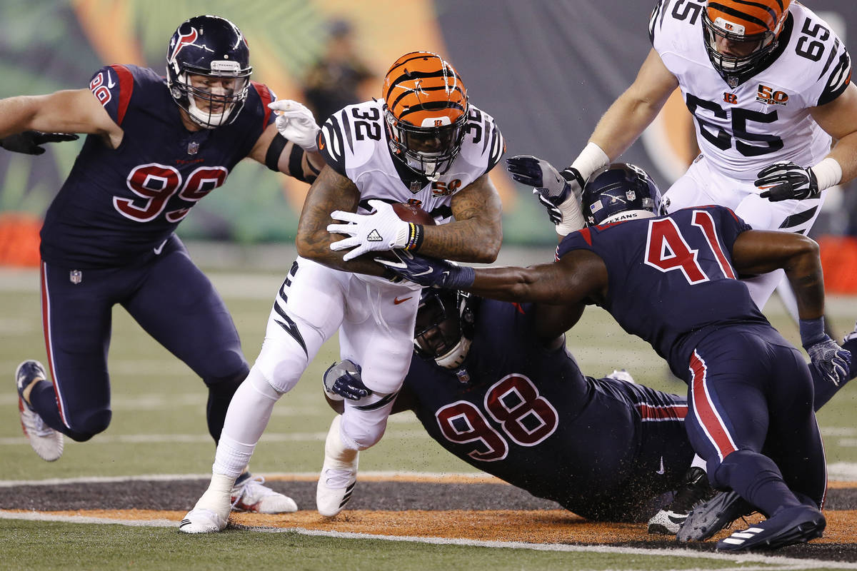 Cincinnati Bengals running back Jeremy Hill (32) carries between Houston Texans nose tackle D.J ...
