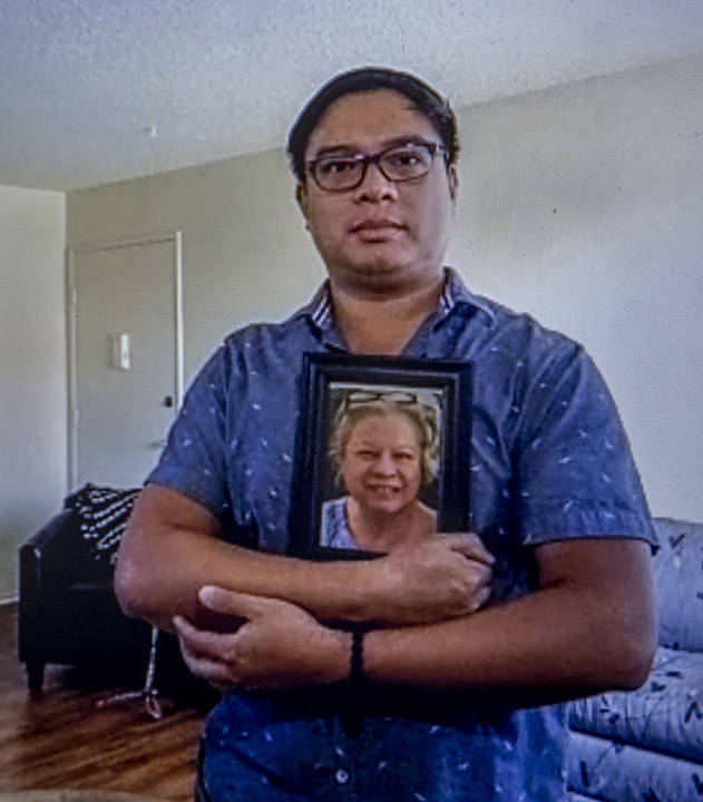 Roderick Alimusa holds a photograph of his mother, Maria Alimusa, at his home in Westminster, C ...