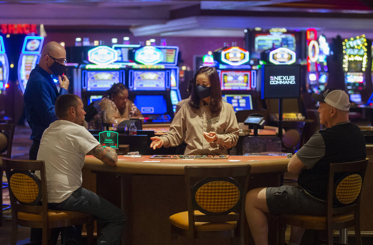 A dealer wearing a protective face mask talks with gamblers playing blackjack at Treasure Islan ...