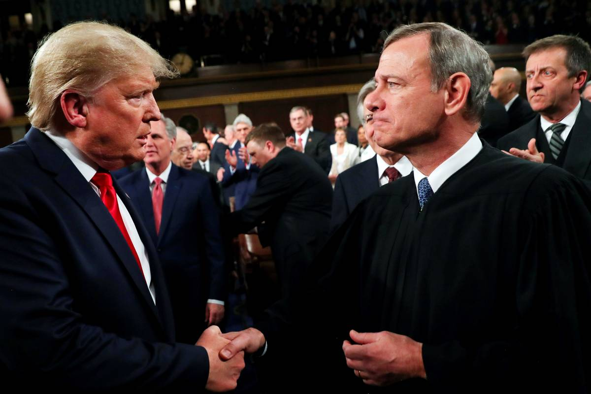 President Donald Trump greets Supreme Court Chief Justice John Roberts as he arrives to deliver ...