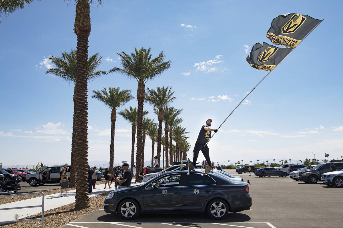 Matt Helfst waves a flag as he waits for the Golden Knights players to pass in buses as they le ...