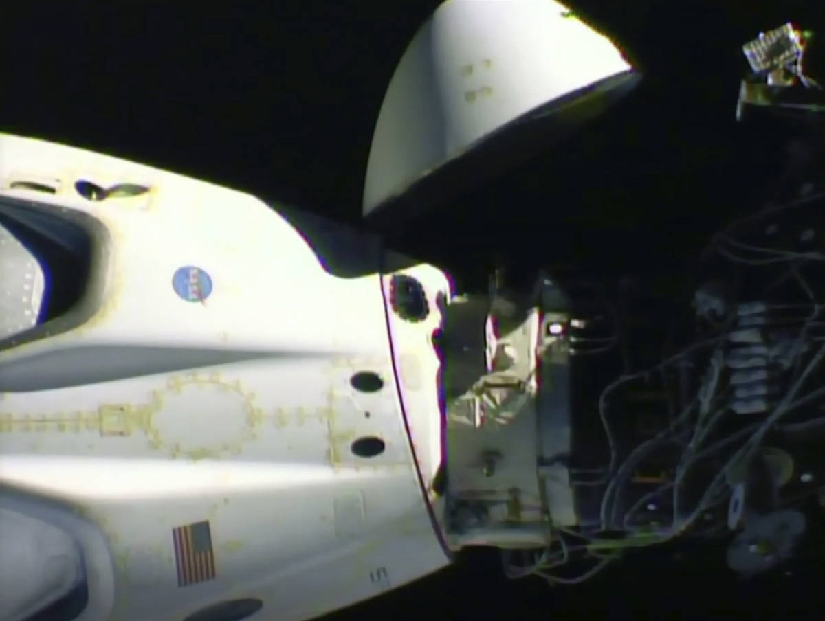 This image from video made available by NASA shows the SpaceX Crew Dragon capsule, left, before ...