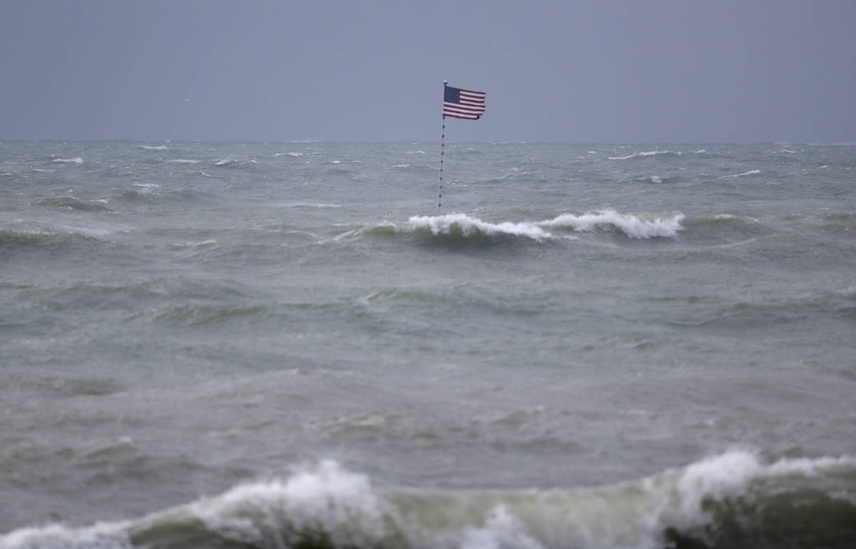 An American flag flies from the shipwreck of the Breconshire, as waves churned up by Tropical S ...