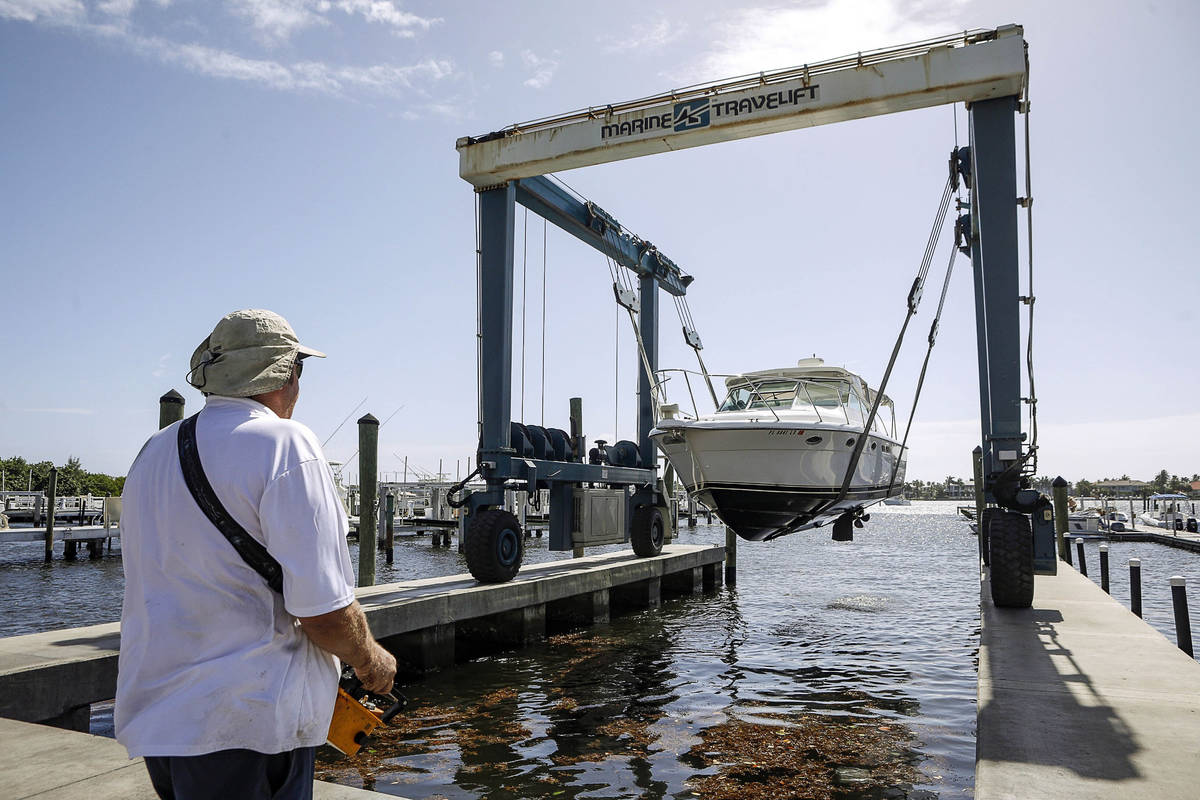 Brett Hand controls a Marine Travelift with a hand held remote to lift boats out of the water a ...