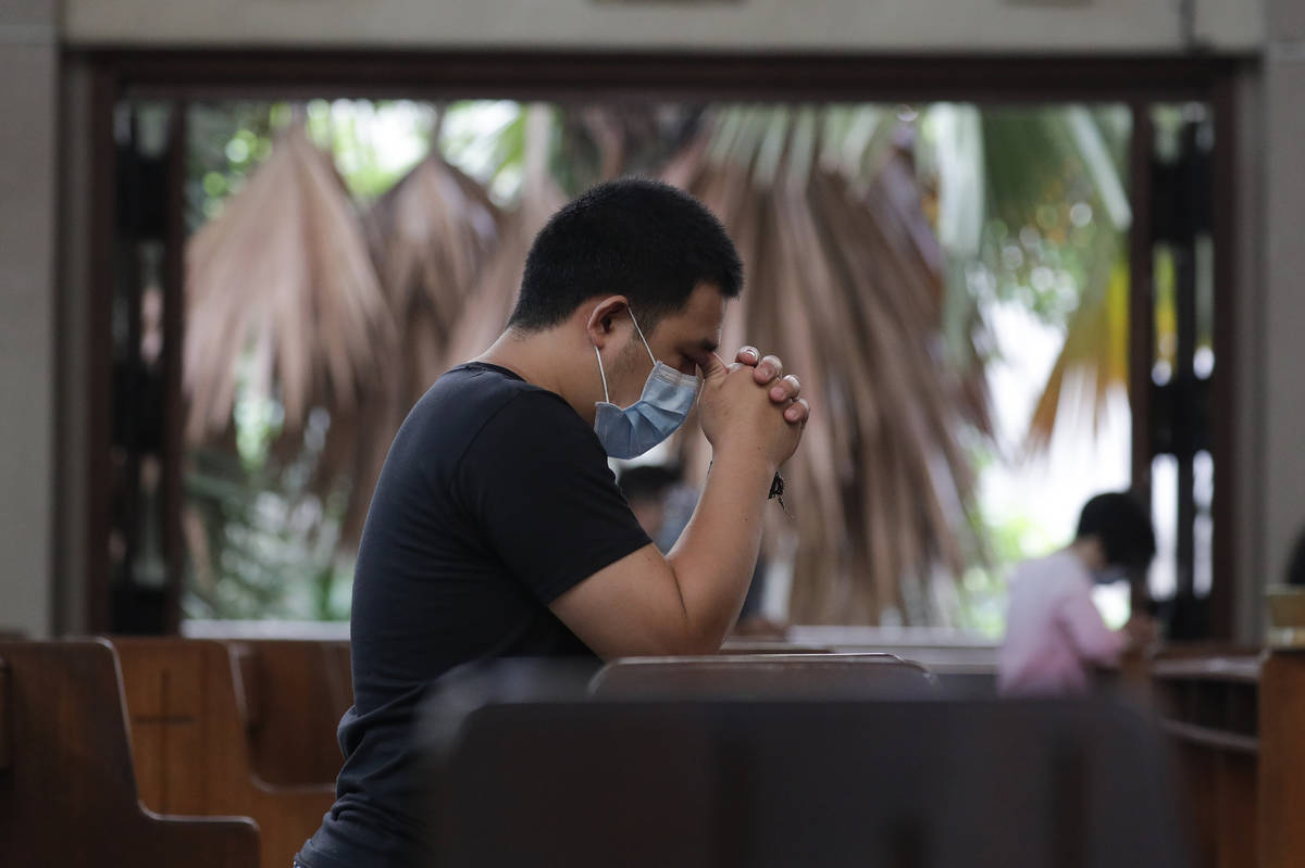 A man prays with only a few other parishioners as a measure to prevent the spread of COVID19 du ...