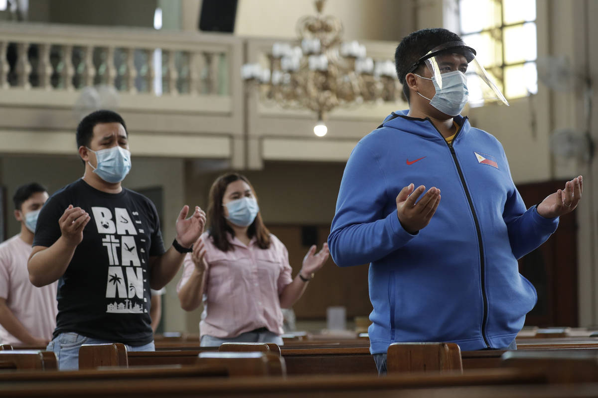 Parishioners wearing masks as a measure to prevent the spread of COVID19 pray during a Mass at ...