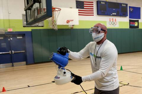 Technician Marc Kmetz of MicroGerm Defense Nevada uses an electrostatic sprayer at James Boys & ...