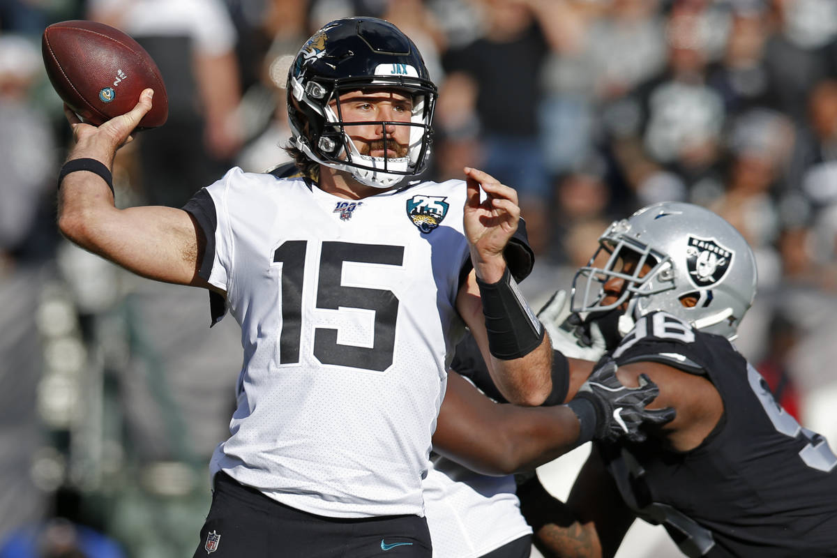 Jacksonville Jaguars quarterback Gardner Minshew throws the ball as Oakland Raiders defensive e ...