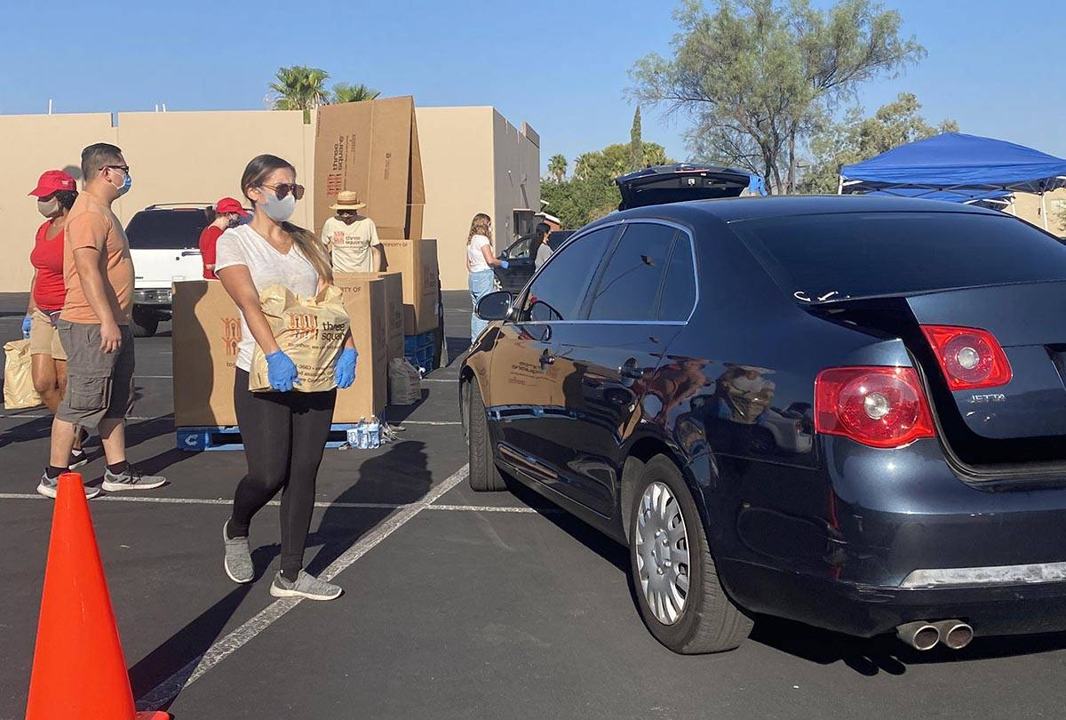 A worker brings food to a car at a food distribution event near North Jones Boulevard and West ...
