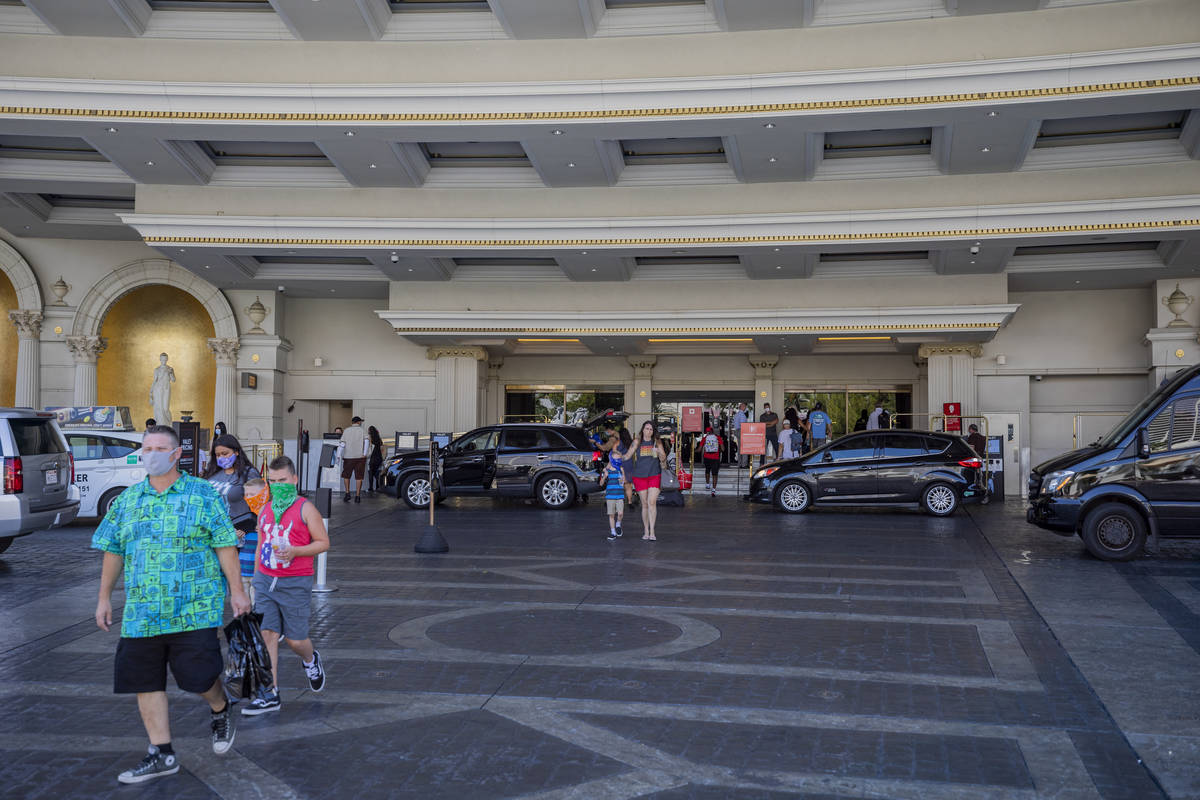 Guests leave Caesars Palace hotel and casino on the Las Vegas Strip, Thursday, Aug. 6, 2020, in ...