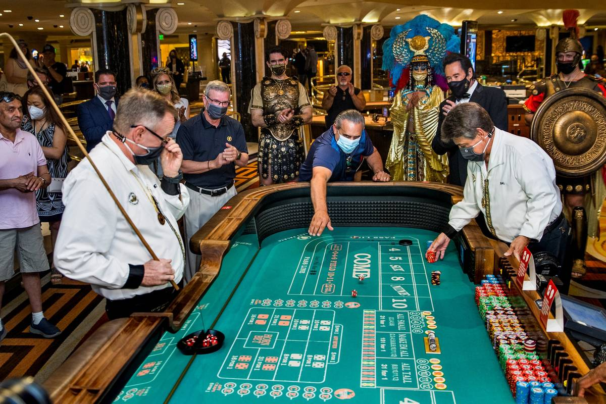 Guest Ben Laparne, center, throws the first dice at a caps table as part of the re-opening cere ...