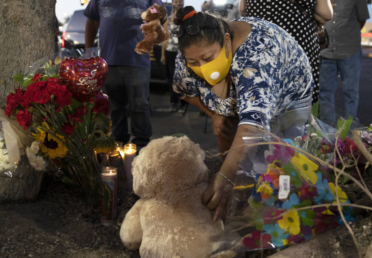 Minerva Rodriguez places a teddy bear with a group of candles during a vigil for Nelly Amaya-Ra ...