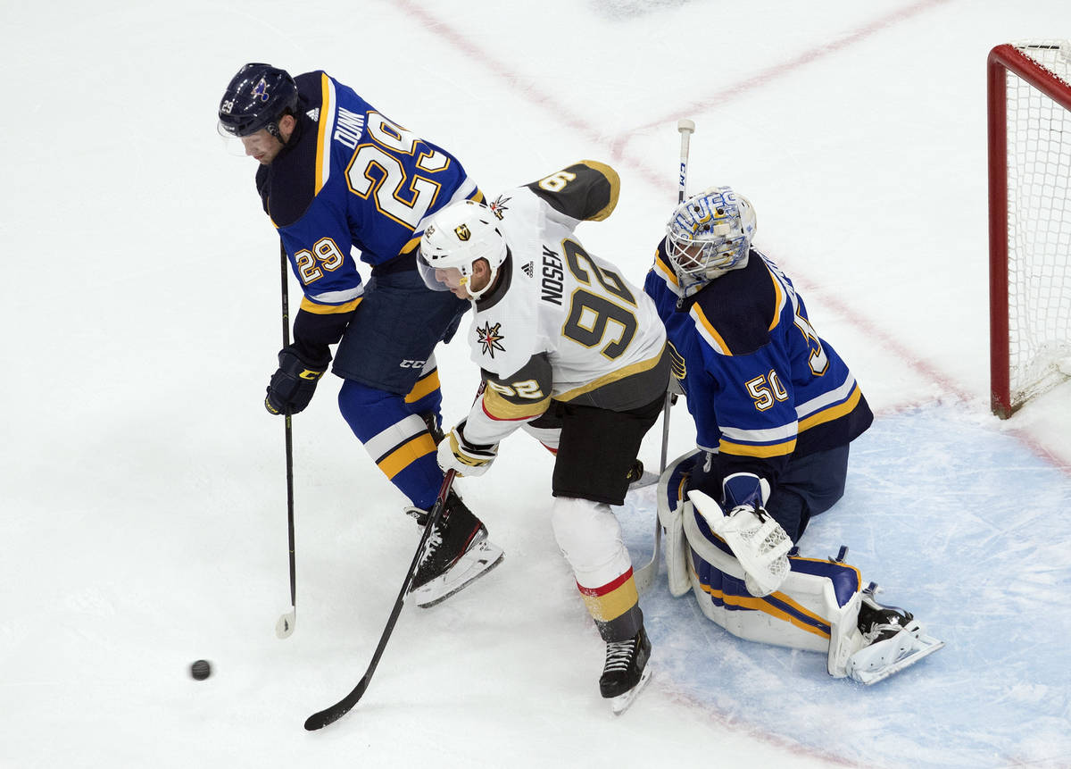St. Louis Blues' Vince Dunn (29) and Vegas Golden Knights' Tomas Nosek (92) battle in front as ...