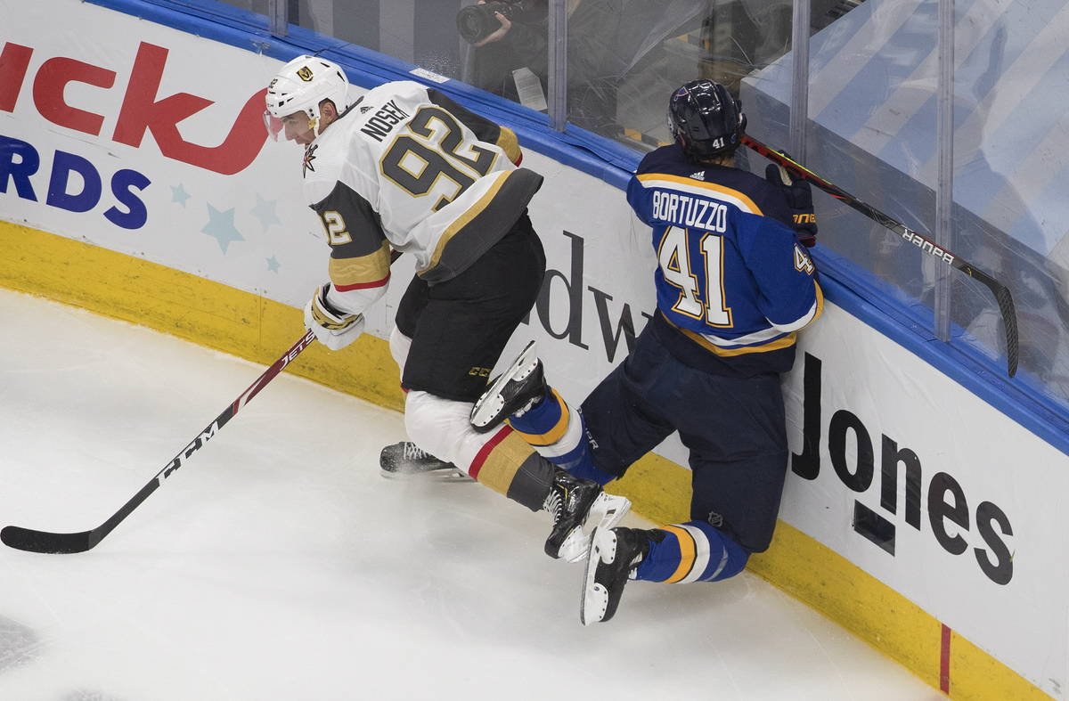 St. Louis Blues' Robert Bortuzzo (41) is checked by Vegas Golden Knights Tomas Nosek (92) durin ...